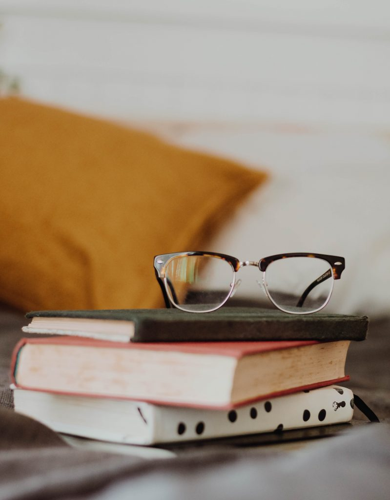 cat eye glasses on stack of 3 books situated on table, mustard yellow pillow out of focus in background