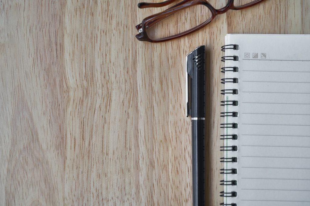 notebook, pen, eye glasses on table